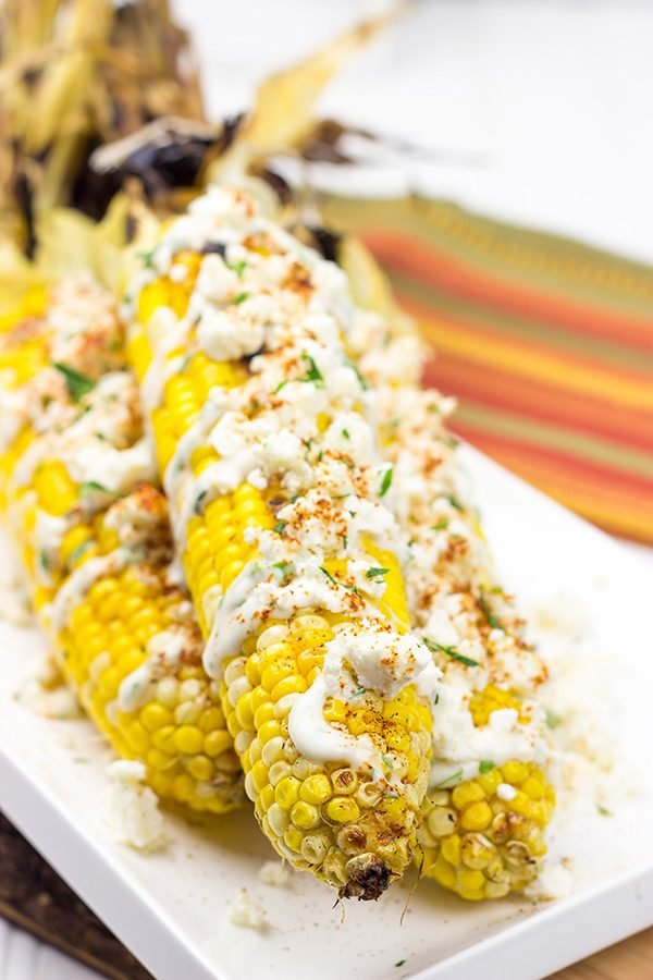 This Mexican Street Corn is covered in crema, grated Parmesan, lime juice and feta cheese. It's messy...and VERY tasty!