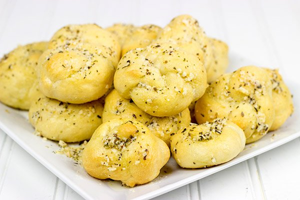 Brushed with melted butter, minced garlic and shaved Parmesan cheese, these Parmesan Garlic Knots are a delicious appetizer for gameday!