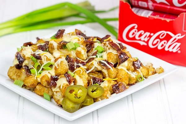 These Loaded Tots are topped with a tasty queso cheese sauce and Coca-Cola glazed bacon bits! They're the perfect snack for watching sports!
