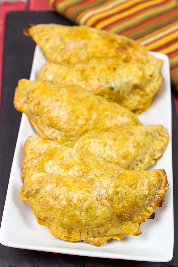 Shredded chicken + cheese + spices all wrapped up in a flaky shell--you can't go wrong with these tasty Cheesy Chicken Empanadas!