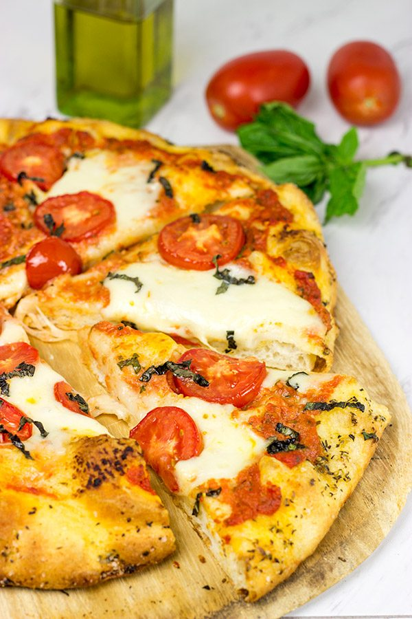 This Classic Pizza Margherita features slices of Roma tomatoes and fresh mozzarella. This recipe is perfect for curling up on the couch and watching a movie!