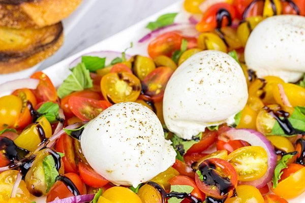 Ever tried burrata cheese? It's in the mozzarella family, and it makes for a great centerpiece of this Tomato and Burrata Caprese!
