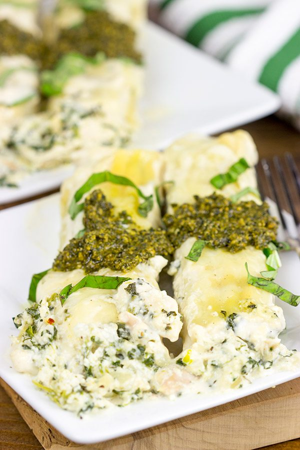 This tasty Pesto Chicken Manicotti is baked in a creamy alfredo sauce and then topped with fresh basil pesto!