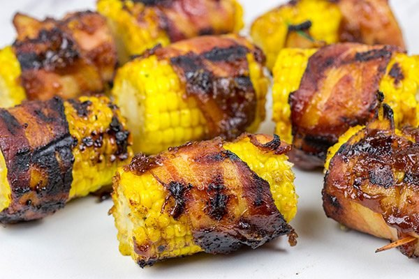 Hunting for a fun side dish for summer grilling?  This Bacon Wrapped Corn with Honey BBQ Sauce is a winner!