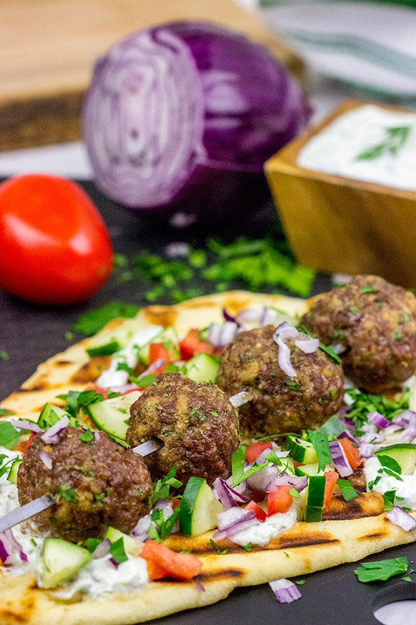 These Mediterranean Meatball Kabobs deserve a spot on your dinner menu soon!  Served up with grilled naan and a bit of tzatziki sauce, these meatballs are sure to become a favorite in your house, too!