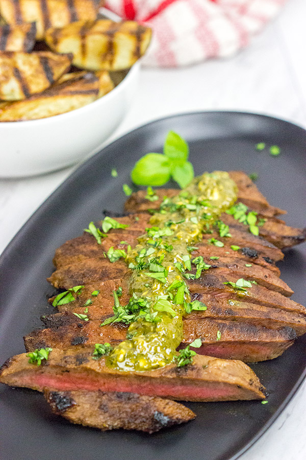 """The flat iron steak is the 2nd most tender cut of beef behind only a tenderloin (aka """"filet mignon""""). Give the flat iron cut a shot with thisMarinated Flat Iron Steak with Pesto Butter recipe!"""