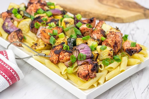 Served over pasta with a bit of grated Parmesan cheese, these Grilled Blackened Chicken Kabobs make for a tasty summer meal!