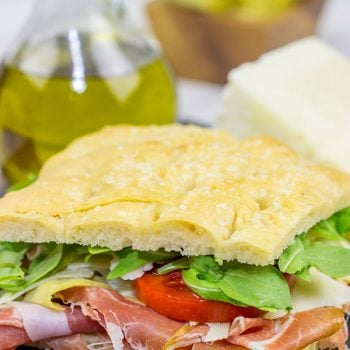 These Italian Prosciutto Panini start with a classic Tuscan bread called schiacciata.  Add in some Prosciutto di Parma, marinated artichokes and Pecorino Romano, and you've got a delicious sandwich!