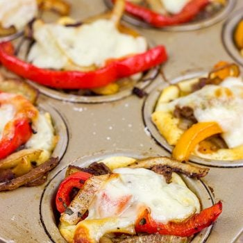 These Philly Cheesesteak Cups feature ribeye steak, peppers and onions all baked in mini crescent roll cups.  They're the perfect comfort food appetizer for football season!