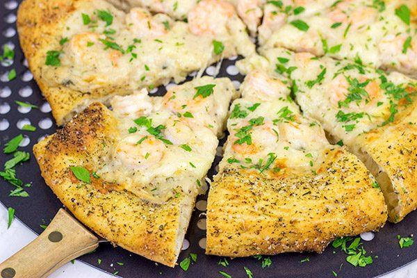 This Shrimp Scampi Pizza is the perfect football food!  Perfectly cooked shrimp combined with a flavorful garlic white sauce make this pizza a tasty option for the big game!