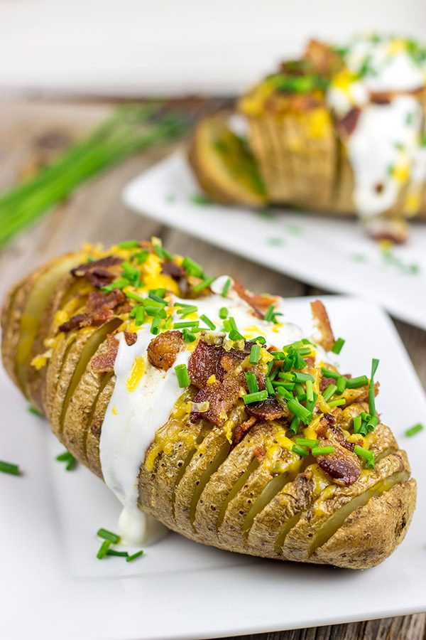 These Loaded Hasselback Baked Potatoes are a fun twist on a baked potato. Crispy edges, soft inside...and they're topped with bacon and cheese!