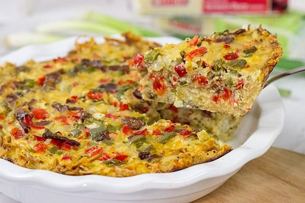 Let's do brunch the right way! This Cheesy Quiche with Hash Brown Crust is loaded with 2 types of cheese, bacon, onions and peppers. Yum!