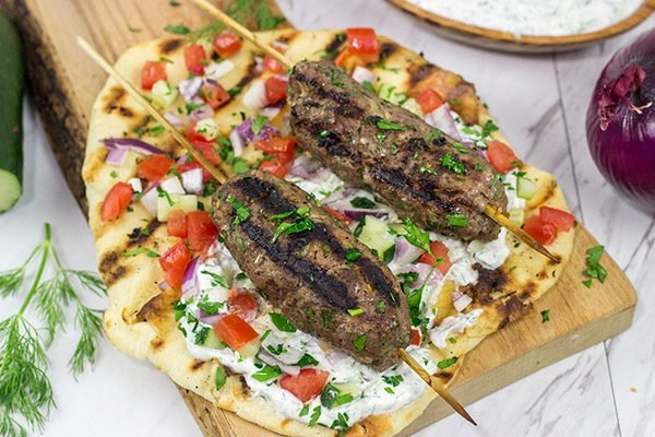 Served over grilled naan and tzatziki sauce, these Grilled Beef Kofta Kabobs are a delicious way to enjoy a summer night in the backyard!