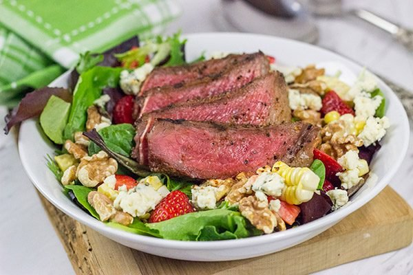 Grilling season is back! Let's kick it off with a delicious Grilled Steak Salad topped with strawberries, blue cheese, corn and toasted walnuts!