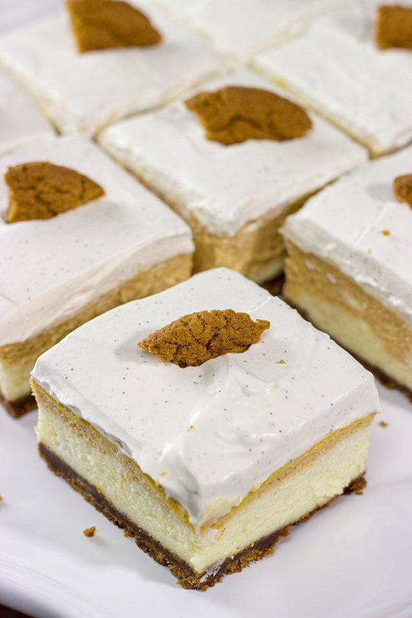 These Pumpkin Swirl Cheesecake Bars feature creamy cheesecake topped with a vanilla bean whipped cream...all over a gingersnap crust! Talk about the perfect Autumn dessert!