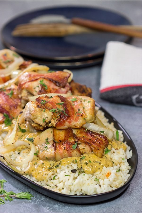These Bacon-Wrapped Chicken Thighs are served over seasoned rice with a Dijon cream sauce. Sounds fancy, right? But this recipe came out of your own kitchen!