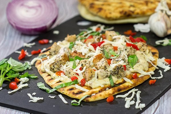 This Grilled Chicken Flatbread features juicy chunks of chicken over a roasted garlic sauce. Served on tasty naan or flatbread, this recipe will have you coming back for more!