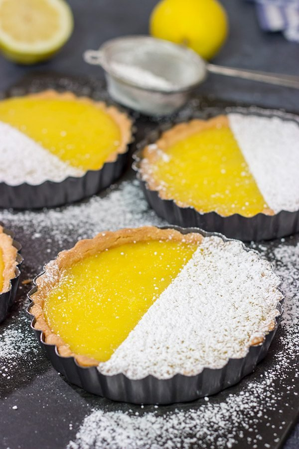 These Lemon Tarts feature a creamy lemon filling inside a crispy sugar cookie crust! Talk about one heck of a delicious dessert!