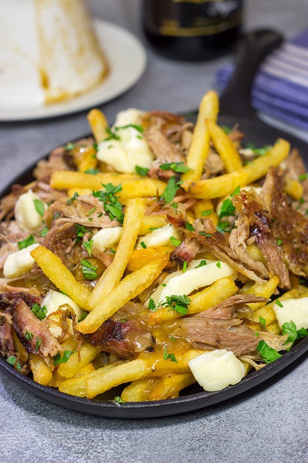 North meets South in this tasty Pulled Pork Poutine recipe. French fries topped with cheese curds, brown gravy and slow-smoked pulled pork make for a delicious appetizer or meal!