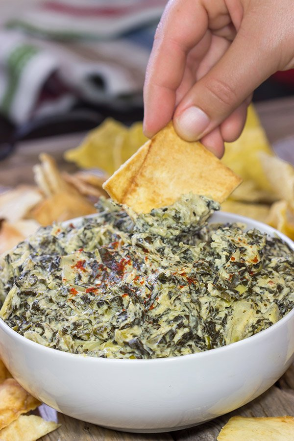 This Slow Cooker Spinach Artichoke Dip is a party favorite! It only takes a few minutes to mix, and then the slow cooker does the rest!
