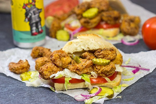 These Fried Shrimp Po'boys are a classic Louisiana sandwich!  A hunk of French bread topped with Cajun fried shrimp, creamy remoulade sauce and shredded lettuce is hard to beat!