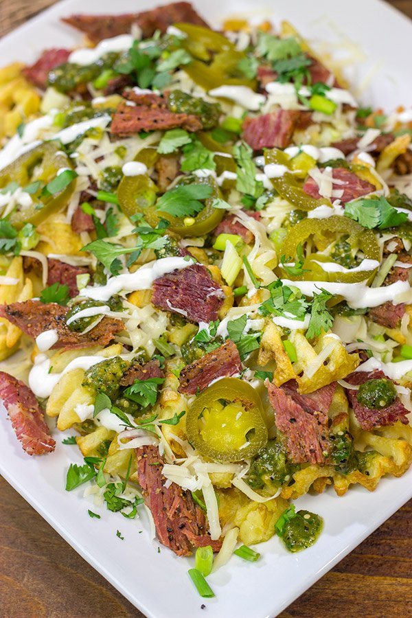 Get into the St. Patrick's Day spirit with a batch of these Irish Nachos - waffle fries loaded with cheese, salsa verde and chopped corned beef!