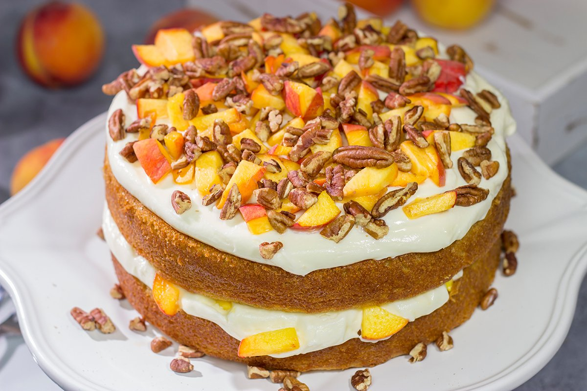 Featuring freshly grated ginger in both the cake as well as the frosting, this Peach Ginger Cake makes for a tasty dessert on a warm summer evening!